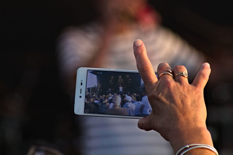 Cropped man photographing with mobile phone during concert