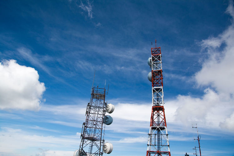Low angle view of repeater towers against sky