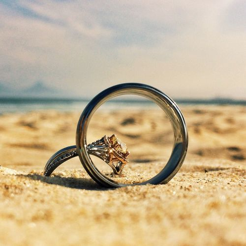 Close-up of wedding rings on sandy beach