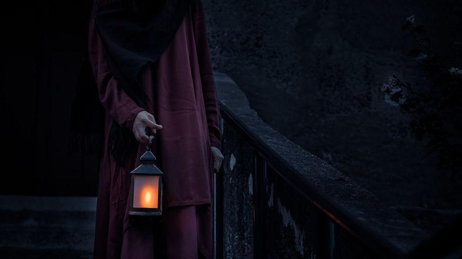 Man standing by illuminated light lantern on building at night