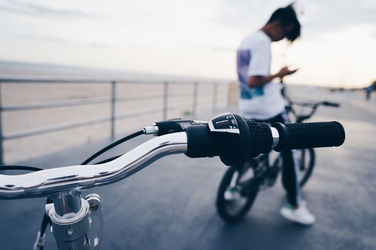 Close-up of bicycle by man on pier