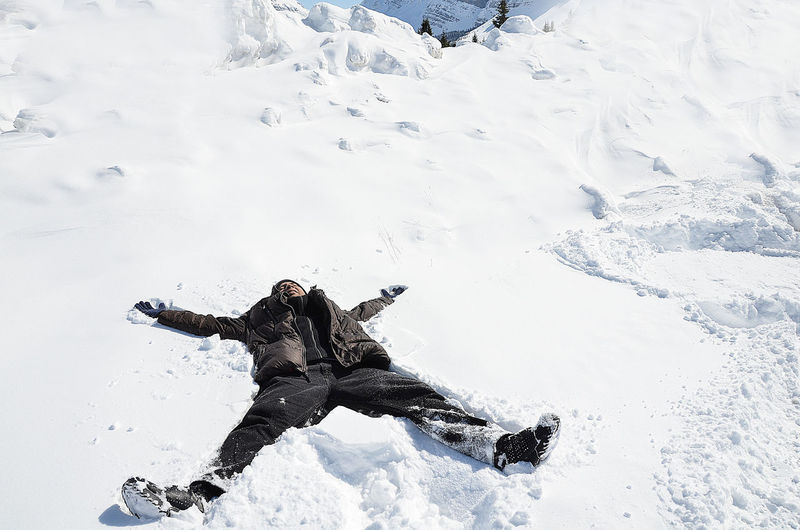 Man Lying Down On Snow Covered Field