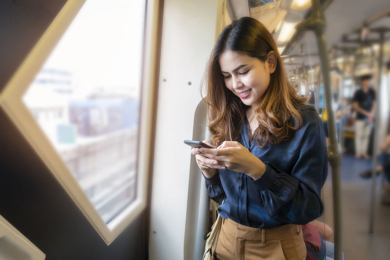 Young woman using phone while standing on mirror