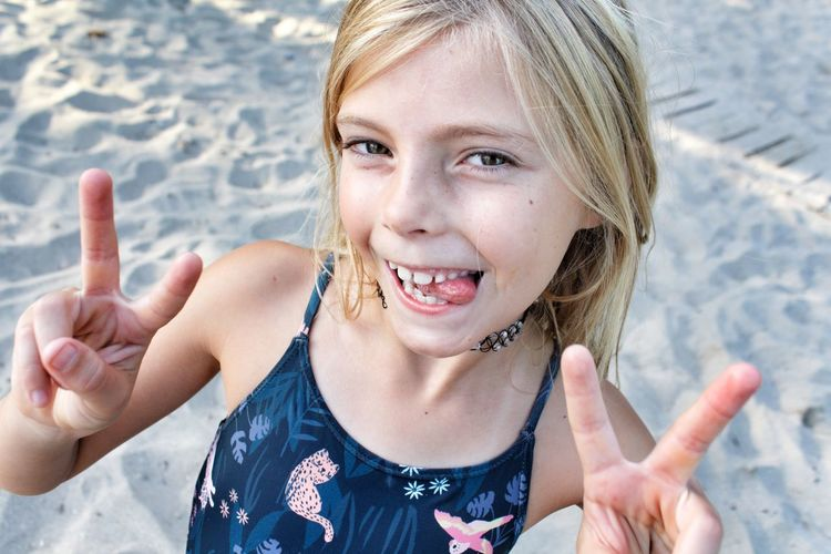 Portrait of smiling girl gesturing at beach