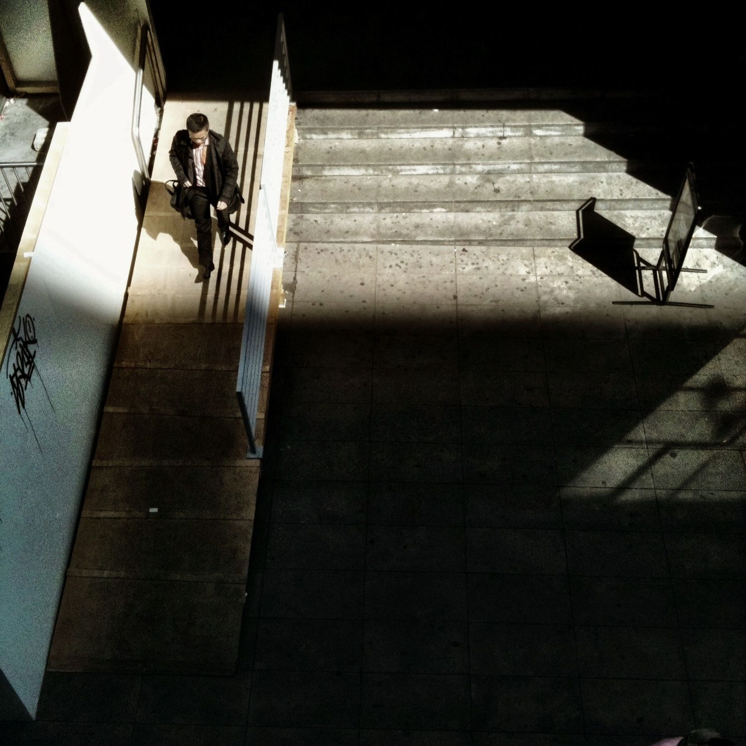 lifestyles, men, leisure activity, full length, indoors, steps, person, sitting, sunlight, built structure, architecture, shadow, walking, togetherness, high angle view, rear view, casual clothing