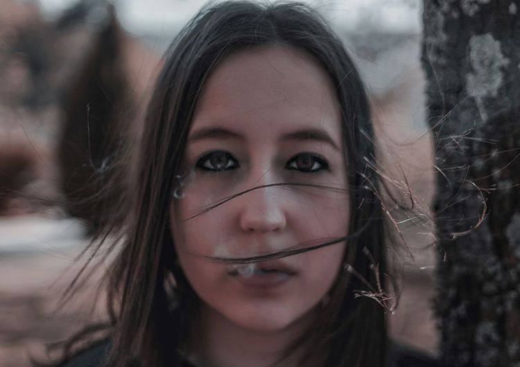Close-up portrait of young woman exhaling smoke
