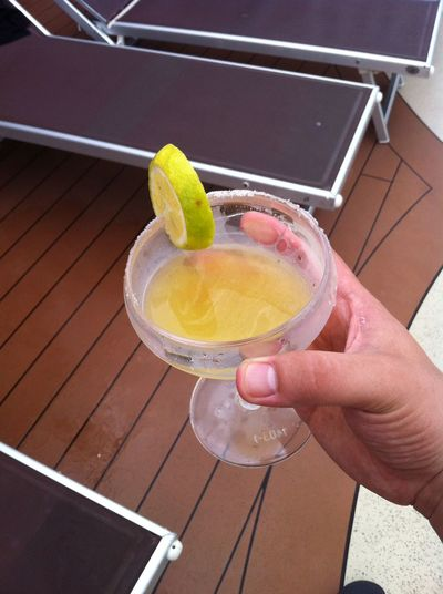 Cropped image of man holding fresh margarita drink on msc poesia
