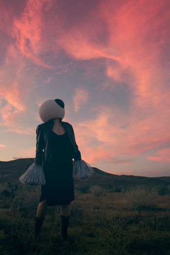 Woman wearing costume while standing on grass against sky during sunset