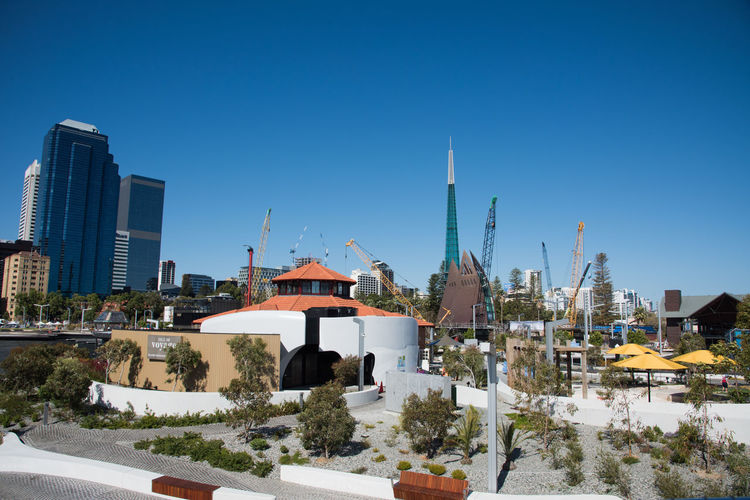 Perth,WA,Australia-November 16,2016: Elizabeth Quay Isle of Voyage restaurant, garden area and view of Swan Bell Tower in Perth, Western Australia. Architecture Bell Tower Blue Building Exterior Built Structure City City Cityscape Construction Site Crane Crane - Construction Machinery Development Elizabeth Quay Garden Industrial Industry Isle Of Voyage Outdoors Restaurant Sky Spire  Swan Bell Tower Tourist Destination Tower Tree