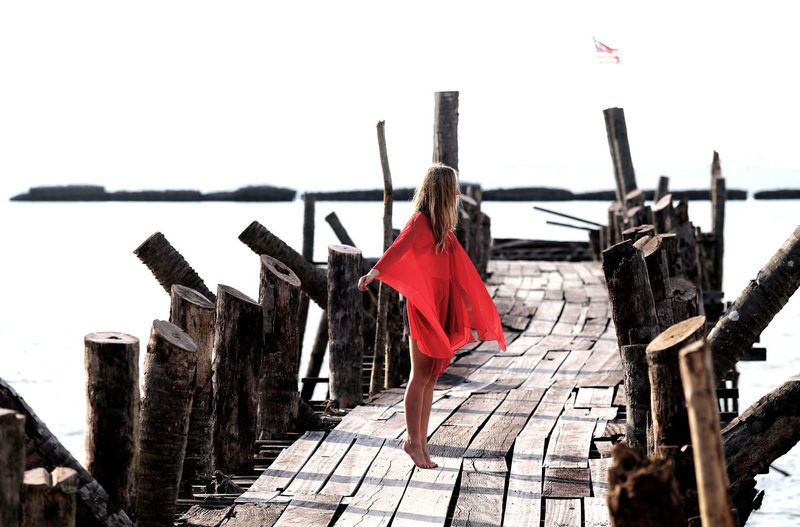 Woman wearing red dress standing on pier over sea against clear sky