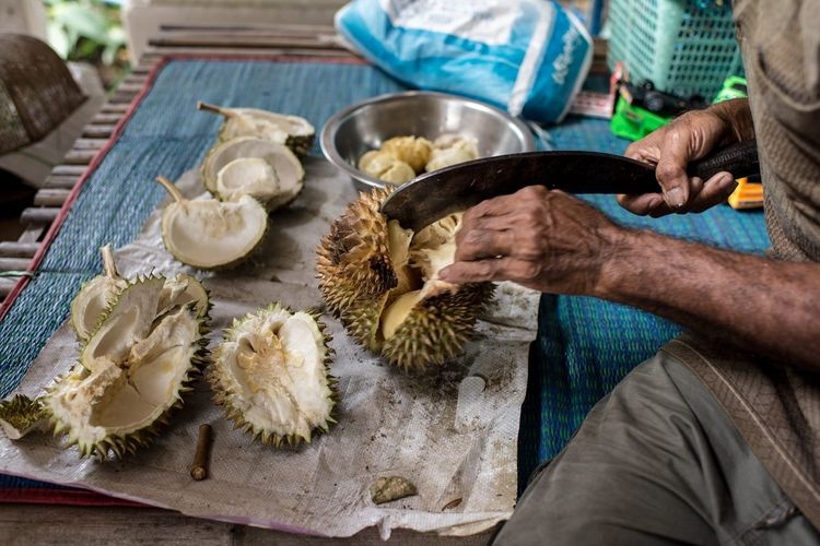 Midsection of man cutting durian on table