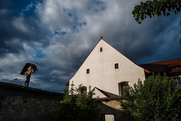 Low angle view of crucifix by church against cloudy sky