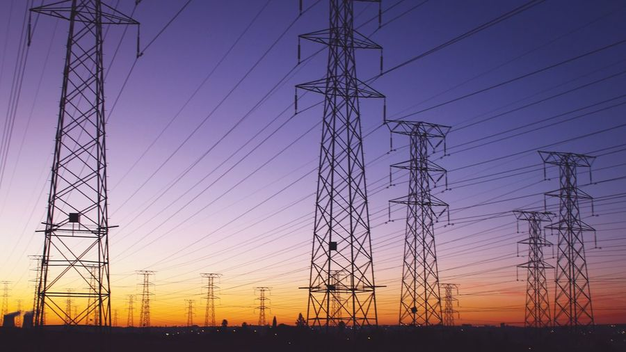 Electricity Pylons Against Sky During Sunset