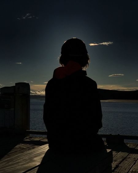 Rear view of silhouette woman looking at sea against sky