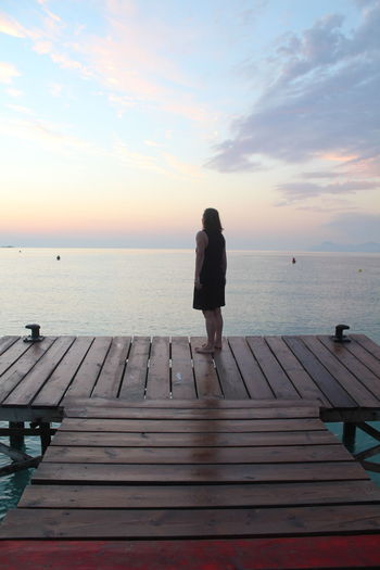 Rear view of woman standing on pier over sea against cloudy sky during sunset