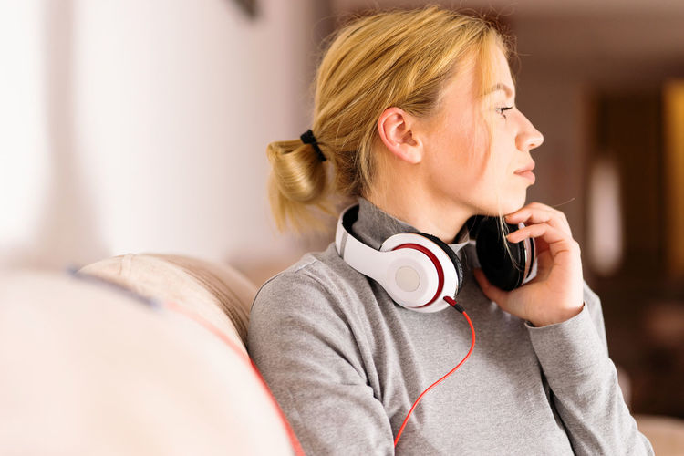 Headphones Listening One Person Music Indoors  Young Adult Lifestyles Young Women Blond Hair Women Adult Real People Headshot Hair Technology Casual Clothing Leisure Activity Home Interior Hairstyle