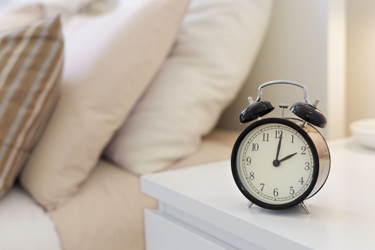 Close-up of clock on table by bed at home