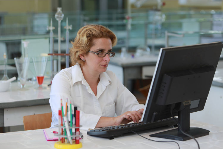 Female researcher working on a computer in a laboratory. Computer One Person Technology Adult Indoors  Real People Blond Hair Eyeglasses  Desktop Workplace Working Browsing Internet Research Researcher Researcher Life Science Scientist Female Woman Lab Laboratory Using Computer Education Studying Study Time Learning University School Chemistry Phisics