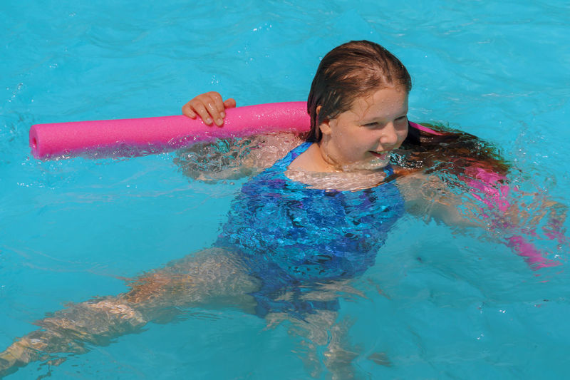 High angle view of girl with noddle looking away in swimming pool
