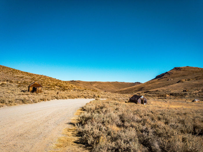 Bodie State Historic Park Adventure Architecture Arid Climate Barren Beauty In Nature Blue Clear Sky Copy Space Day Desert Land Vehicle Landscape Mountain Nature One Person Outdoors People Real People Remote Road Rural Scene Scenics Sky The Way Forward Transportation