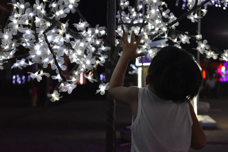 Rear view of girl standing by christmas tree