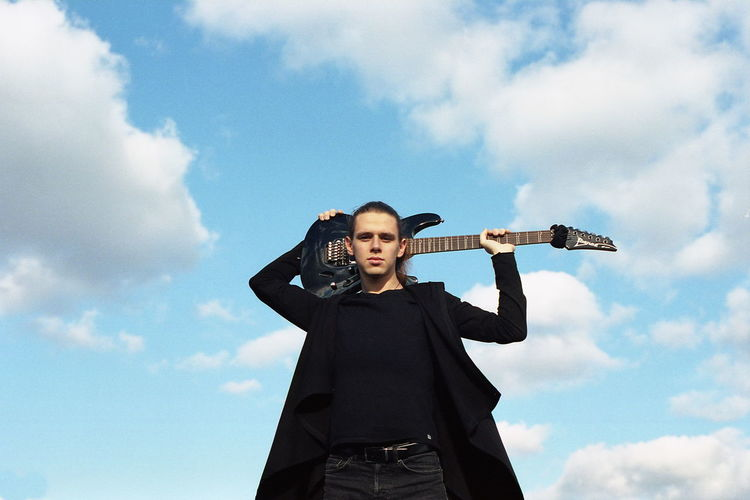 Low angle portrait of young man holding guitar against sky