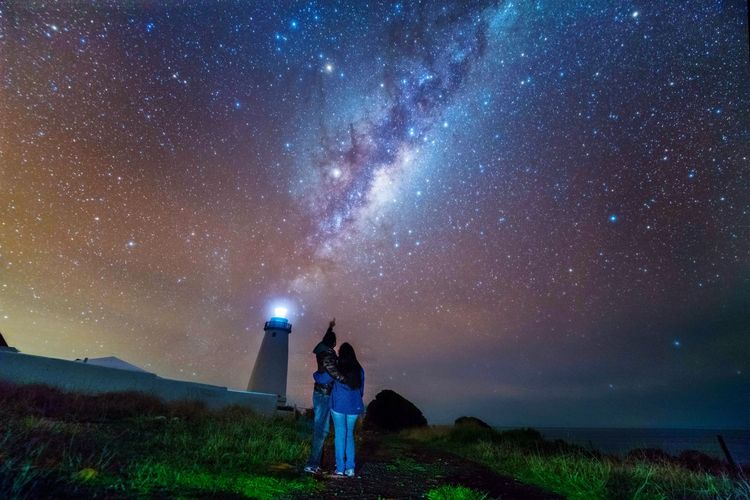 Low angle view of couple standing against star field