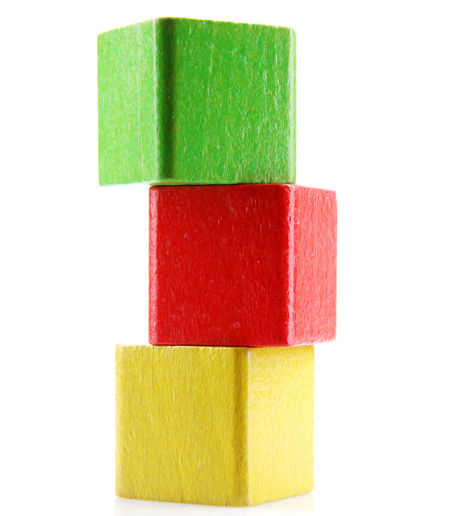 Close-up of multi colored wooden blocks stacked against white background