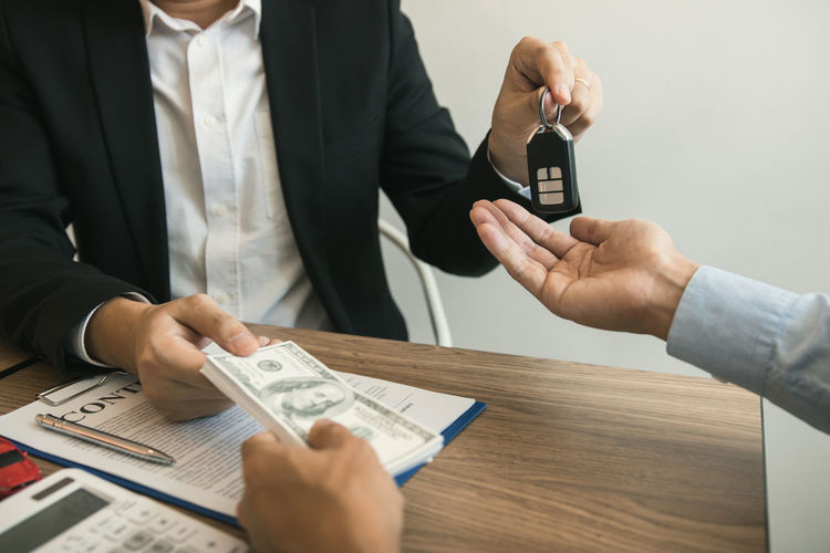 Midsection of man receiving money while giving car key to customer on table