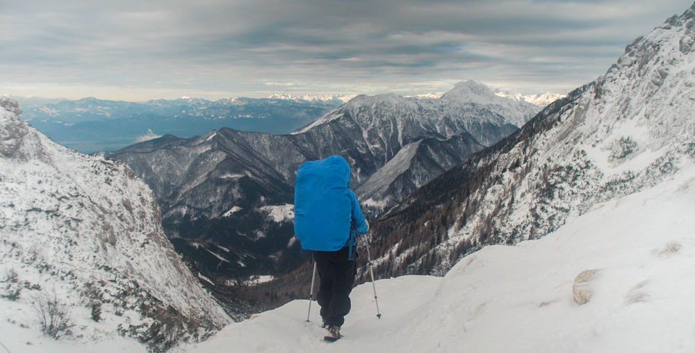 Rear View Of Person On Snowcapped Mountains Against Sky