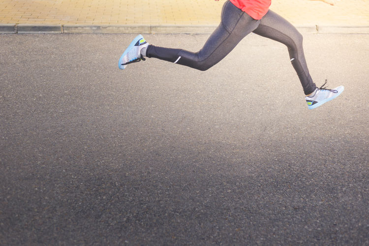 Low section of person running on road. young man sprinting on pavement. speed concept
