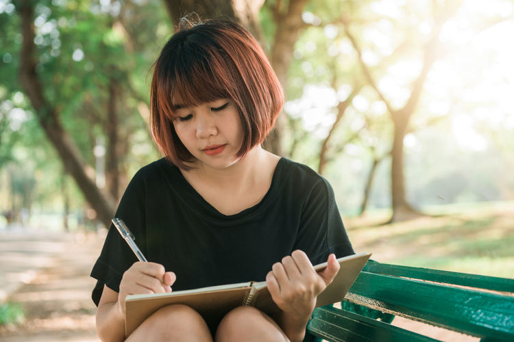 Young woman looking away while sitting on bench