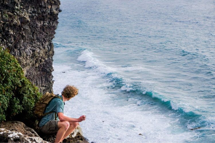 Man Sitting On Rock Formation By Sea