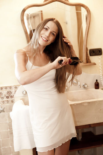 young attractive single woman tourist in spain Beautiful Woman Day Home Interior Home Showcase Interior Indoors  Leisure Activity Lifestyles Long Hair Looking At Camera Mirror One Person Portrait Real People Smiling Standing Three Quarter Length Young Adult Young Women