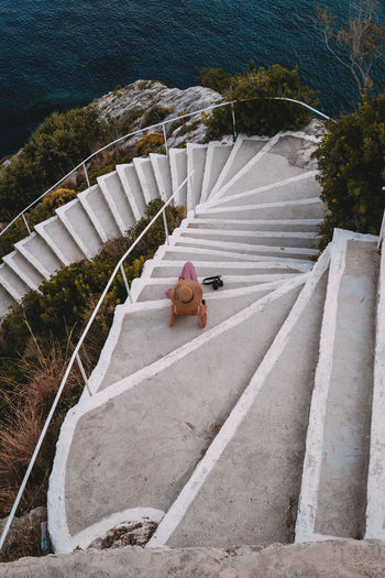 High angle view of woman sitting on staircase by sea