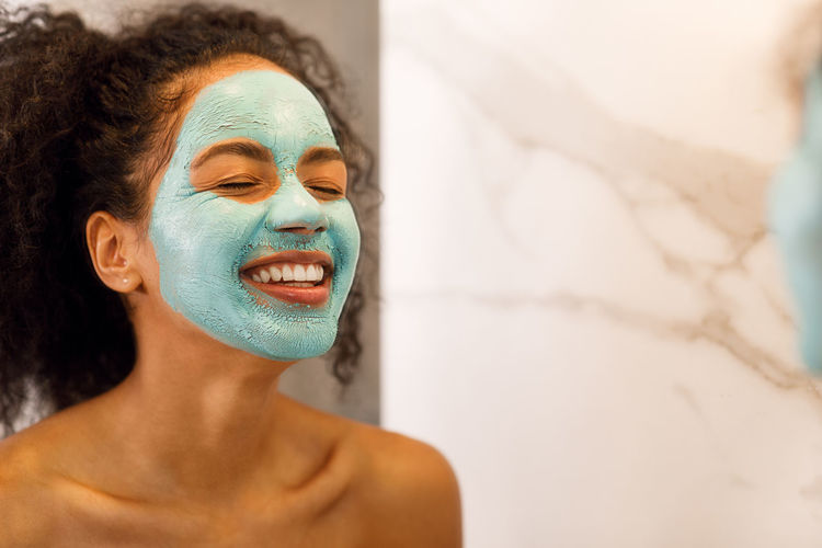 Close-up of smiling woman with facial mask
