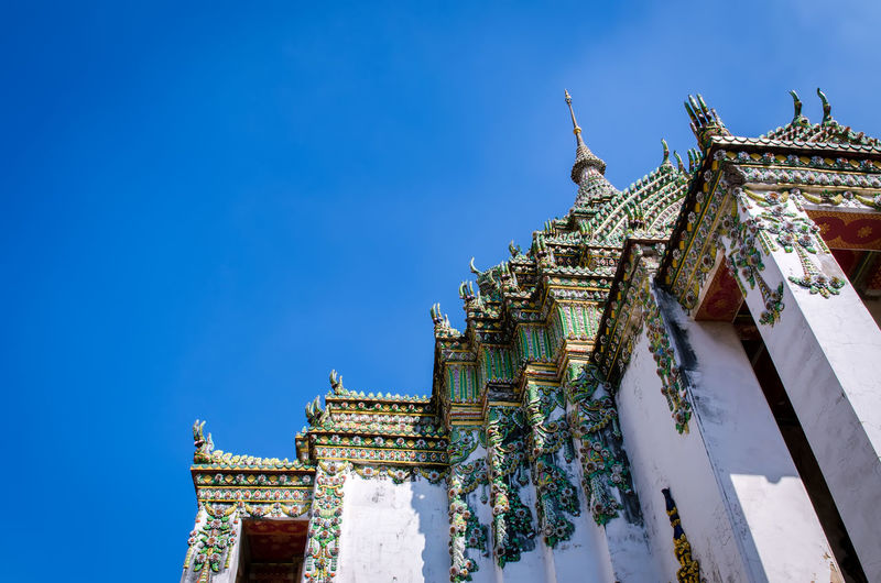 Low angle view of wat pho temple against clear blue sky