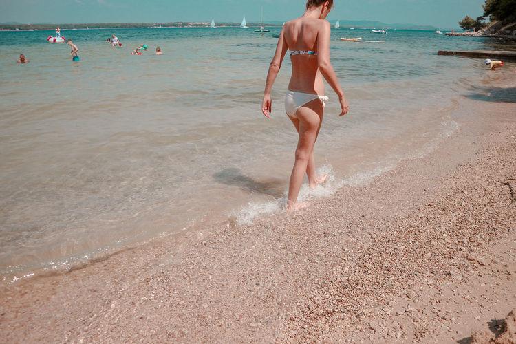 Full length of shirtless man jumping on beach