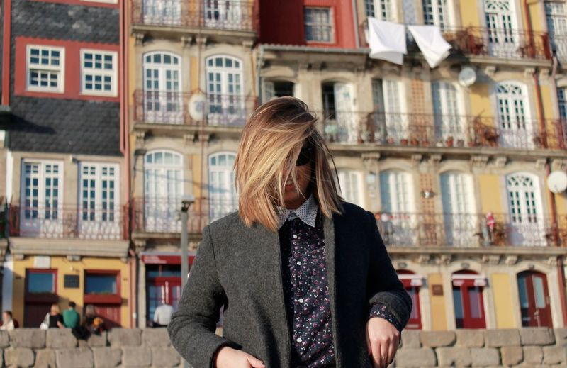 Woman with blond hair standing against buildings