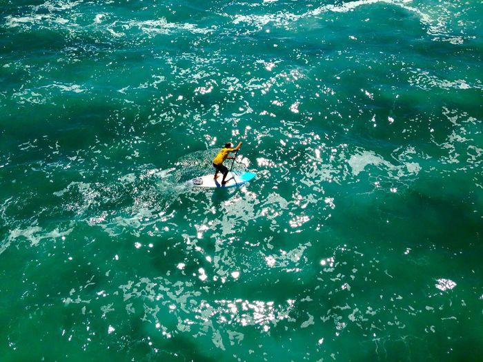 High angle view of man paddleboarding at sea