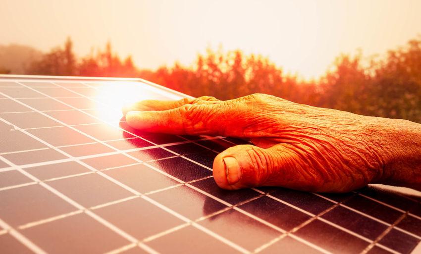 Close-up of hand holding orange during sunset