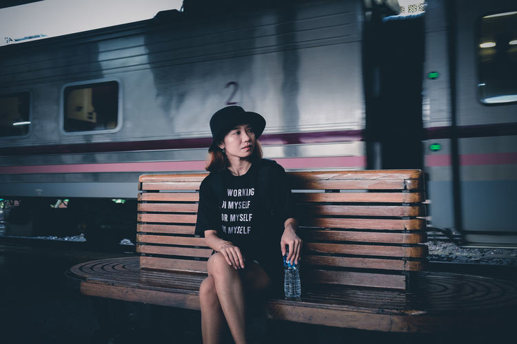 Young woman sitting on bench at railroad station platform