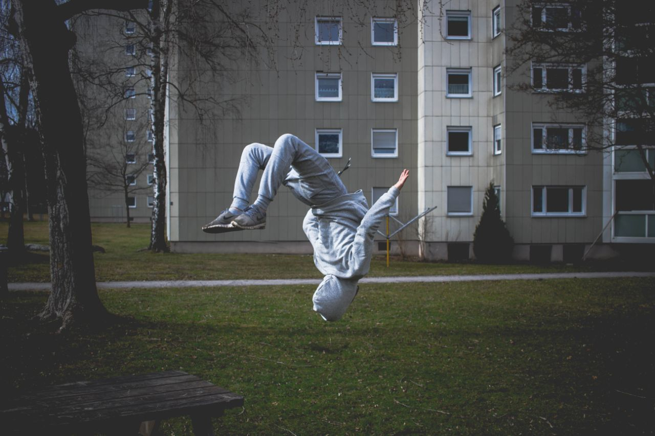 LOW SECTION OF MAN JUMPING AGAINST BUILDING