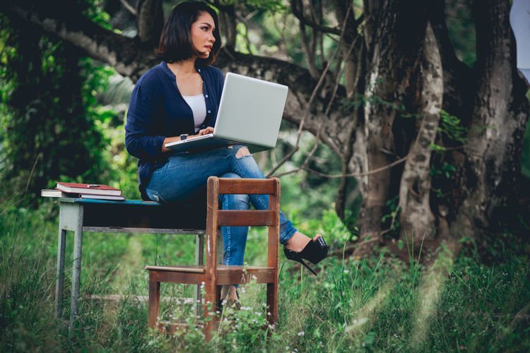Full length of woman using laptop while sitting at park