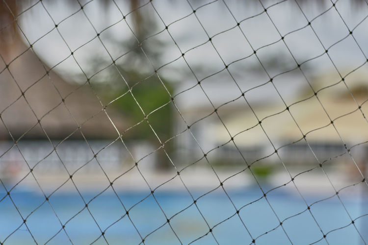 Focus On Foreground No People Fence Pattern Day Full Frame Net - Sports Equipment Close-up Security Protection Backgrounds Safety Nature Barrier Boundary Outdoors Selective Focus Sky Chainlink Fence Netting