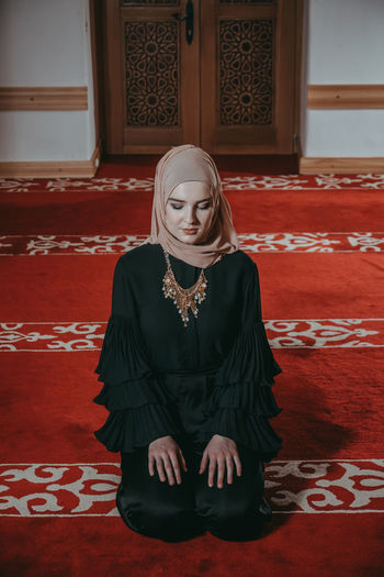 Woman in traditional clothing praying at mosque