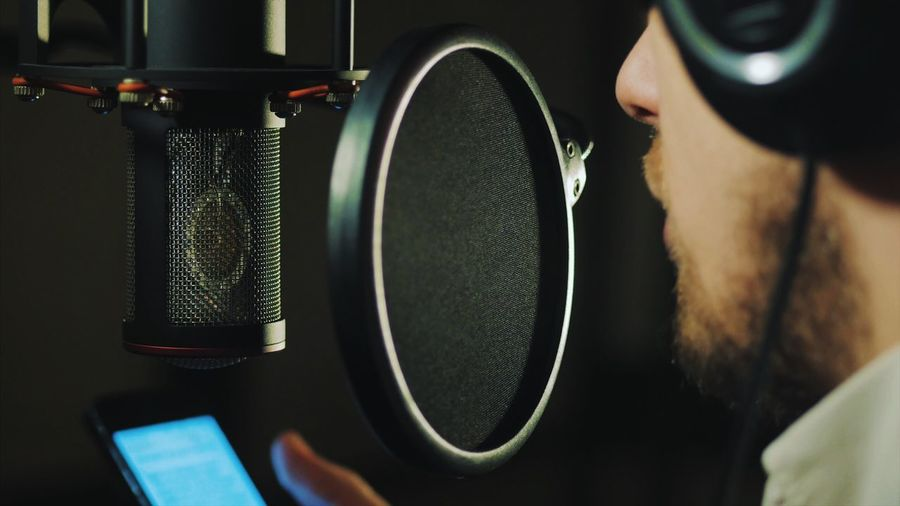 Close-up of man singing at recording studio