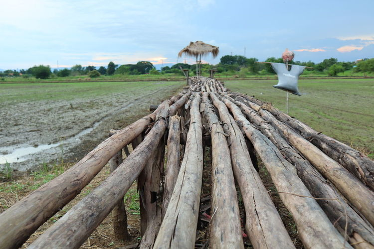 Wooden structure on field against sky