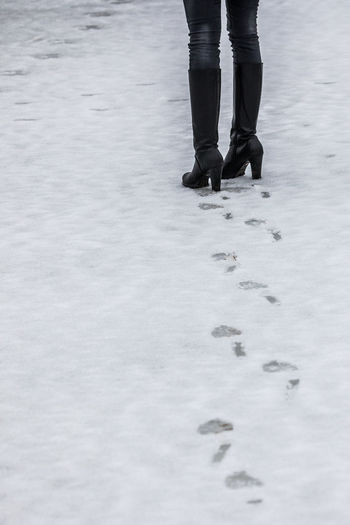 Low section of woman walking on snow covered field