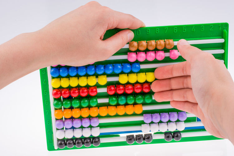 Close-up of hand holding abacus over white background